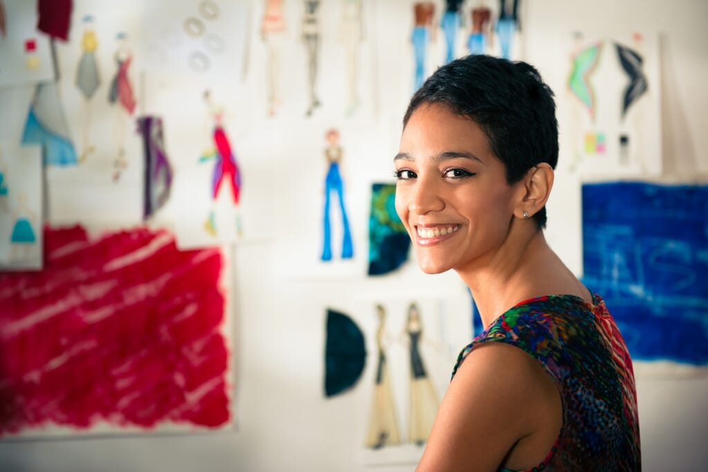 Portrait Of Happy Hispanic Young Woman Working As Fashion Design